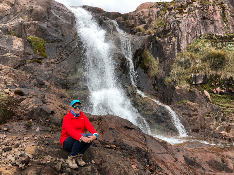 Author sitting beside a waterfall on the Hucahuasi hike