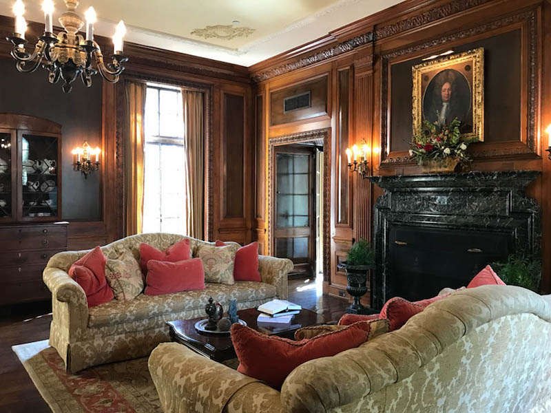 Georgian Revival-style living room featuring the original fireplace mantle, bronze and iron chandeliers, and sconces (Photo credit: Mary Gilbert)