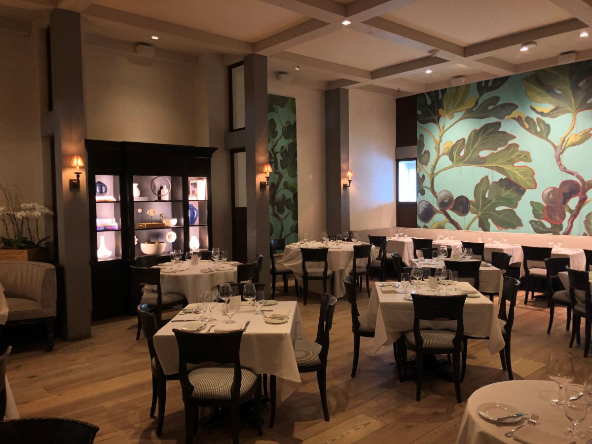The main dining room at Artisan restaurant in West Hartford, CT showing tablecloth-covered tables, chairs, and a large wall mural.