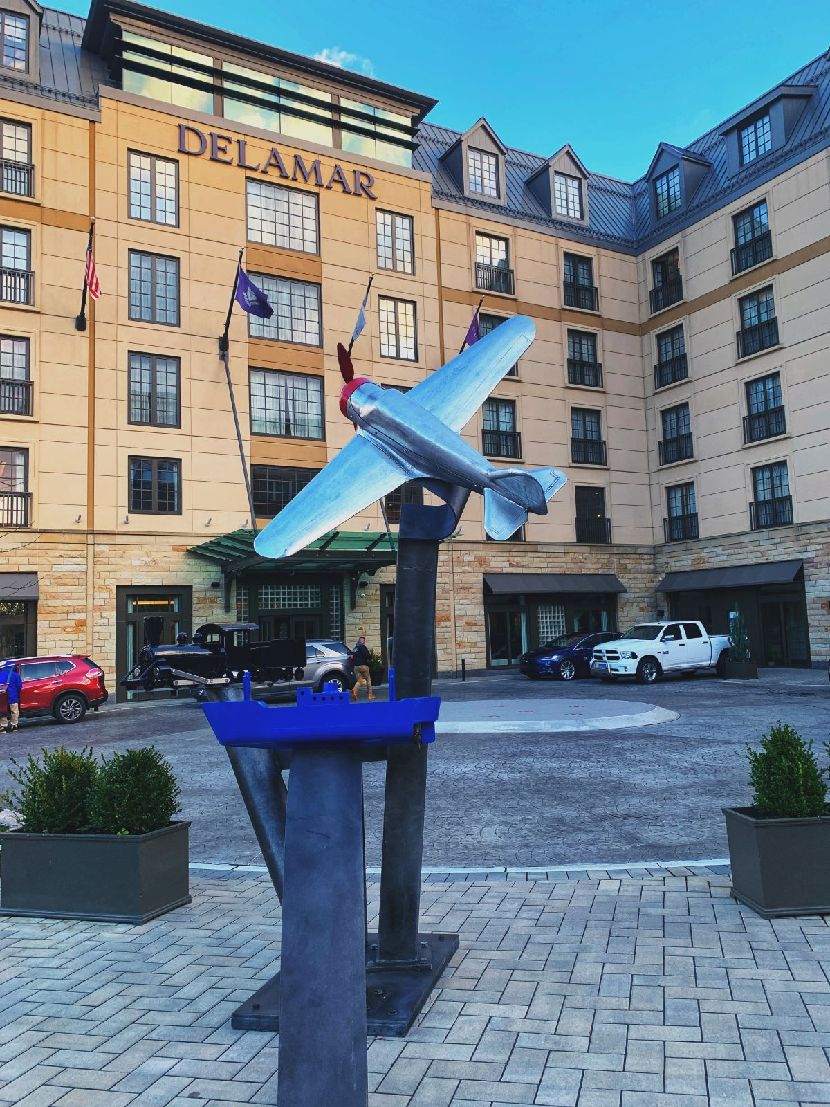 The exterior of the Delamar hotel in West Hartford, CT. An artistic rendering of a plane before the hotel's circular driveway is depicted.
