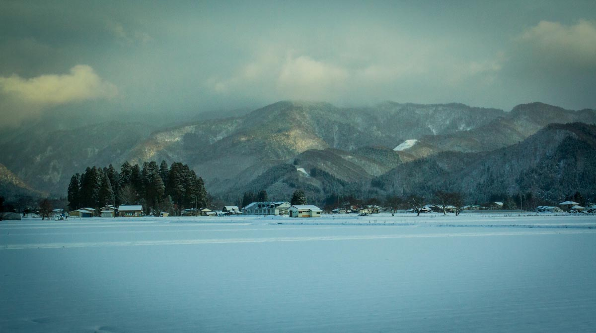 Scenes from the bullet train with Japanese villages surrounded by mountain ranges