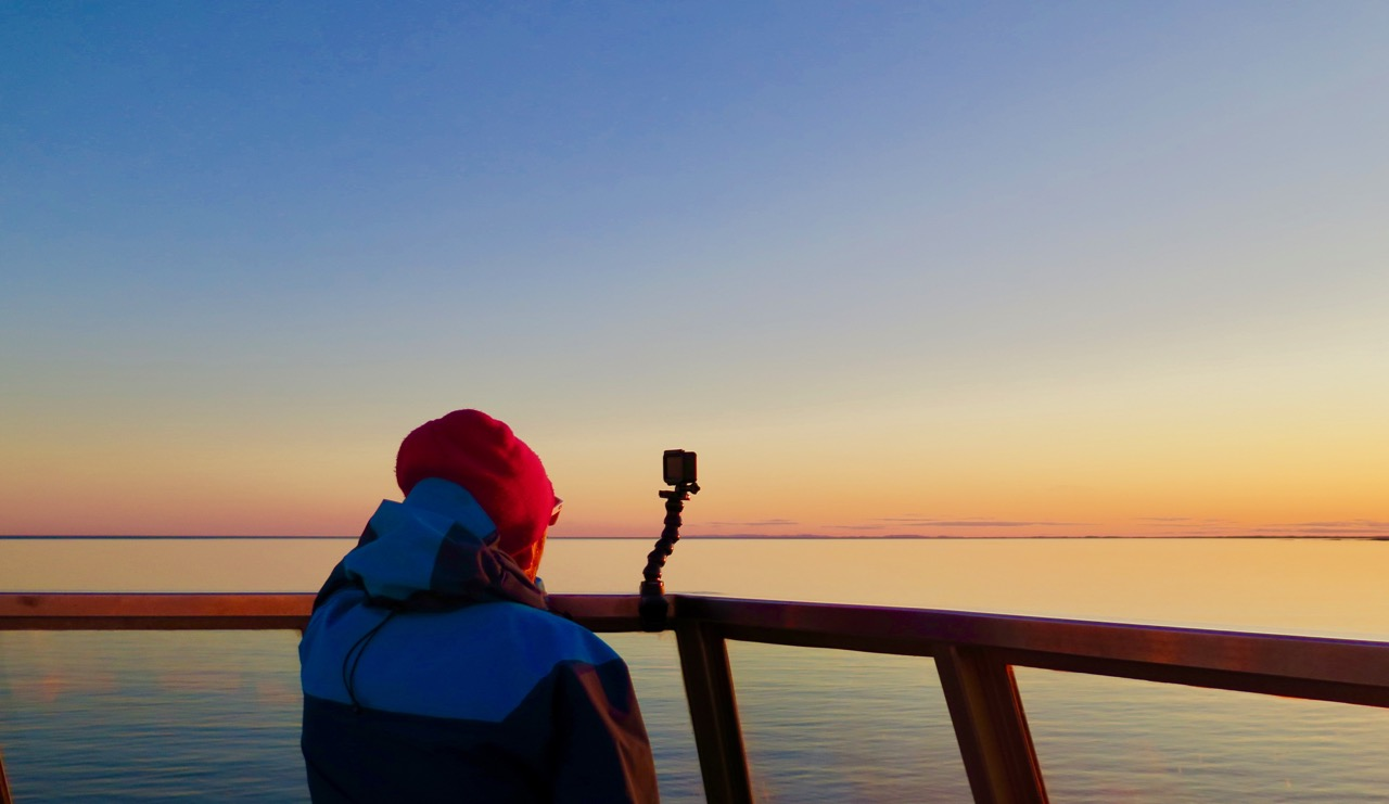 photographer watching sunset on the St. Lawrence River, Quebec, aboard the deck of the Bella Degagnes