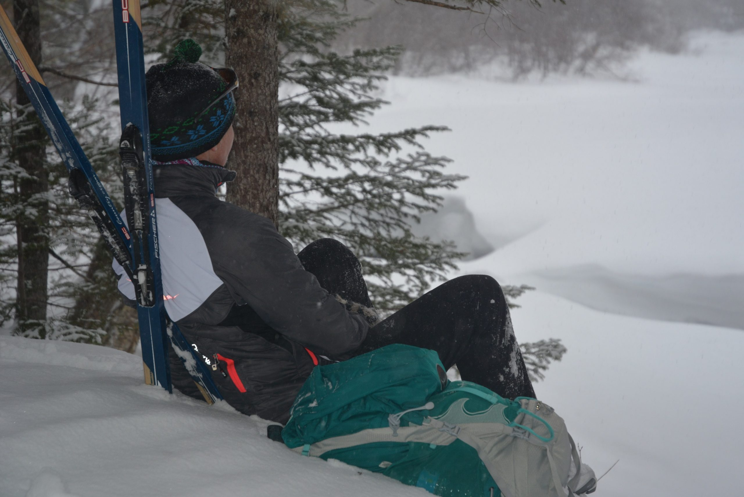 a skier enjoys a break while lodge-to-lodge cross country skiing