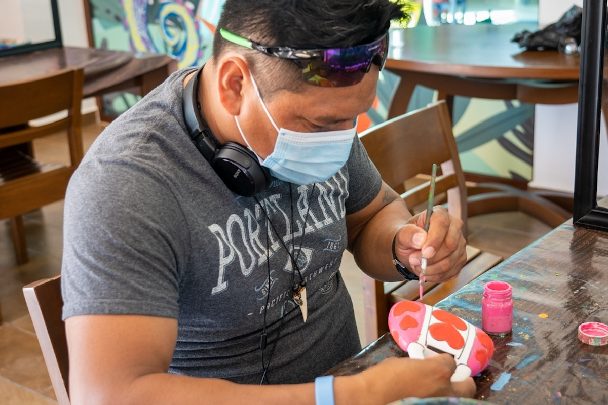 Author's fiancé Weninger enjoys painting a clay figurine at Grand Residences