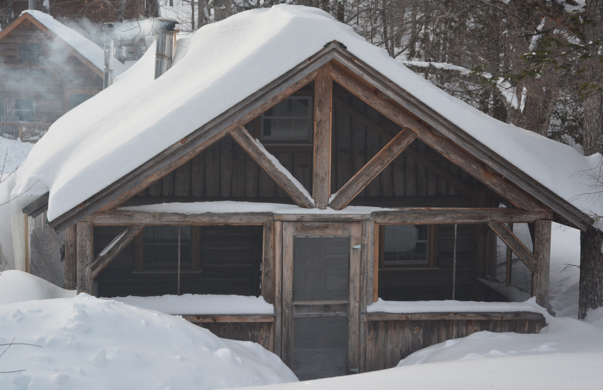 Heavy snow blankets a cabin at Little Lyford, one of the options for a lodge-to-lodge, cross-country skiing adventure