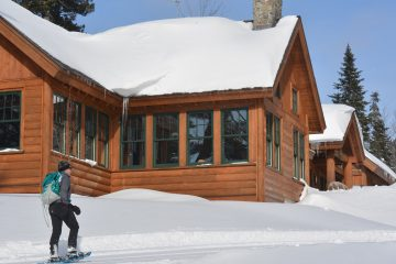A person snowhoes toward the AMC Gorham Chairback main lodge