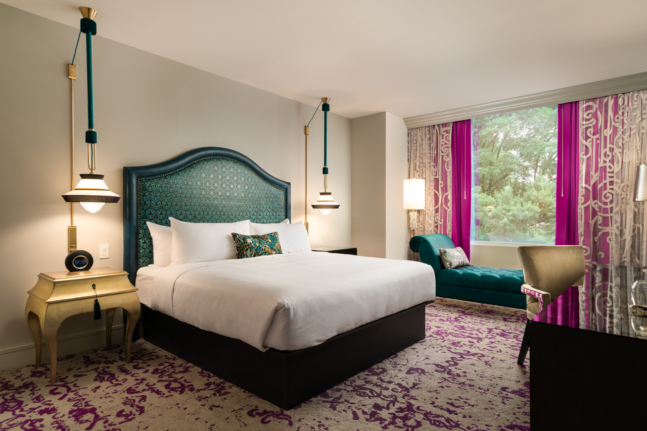 King guestroom with bed and window seat in the Grand Bohemian Hotel Charlotte, one of 202's new hotels and refreshed luxury accommodations