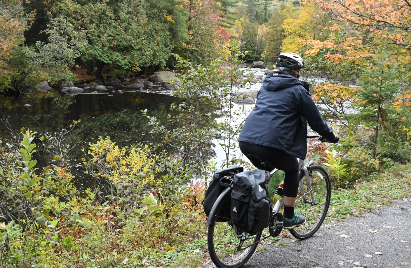 bicyclist pedals by the river on the P'tit du Nord bike trail