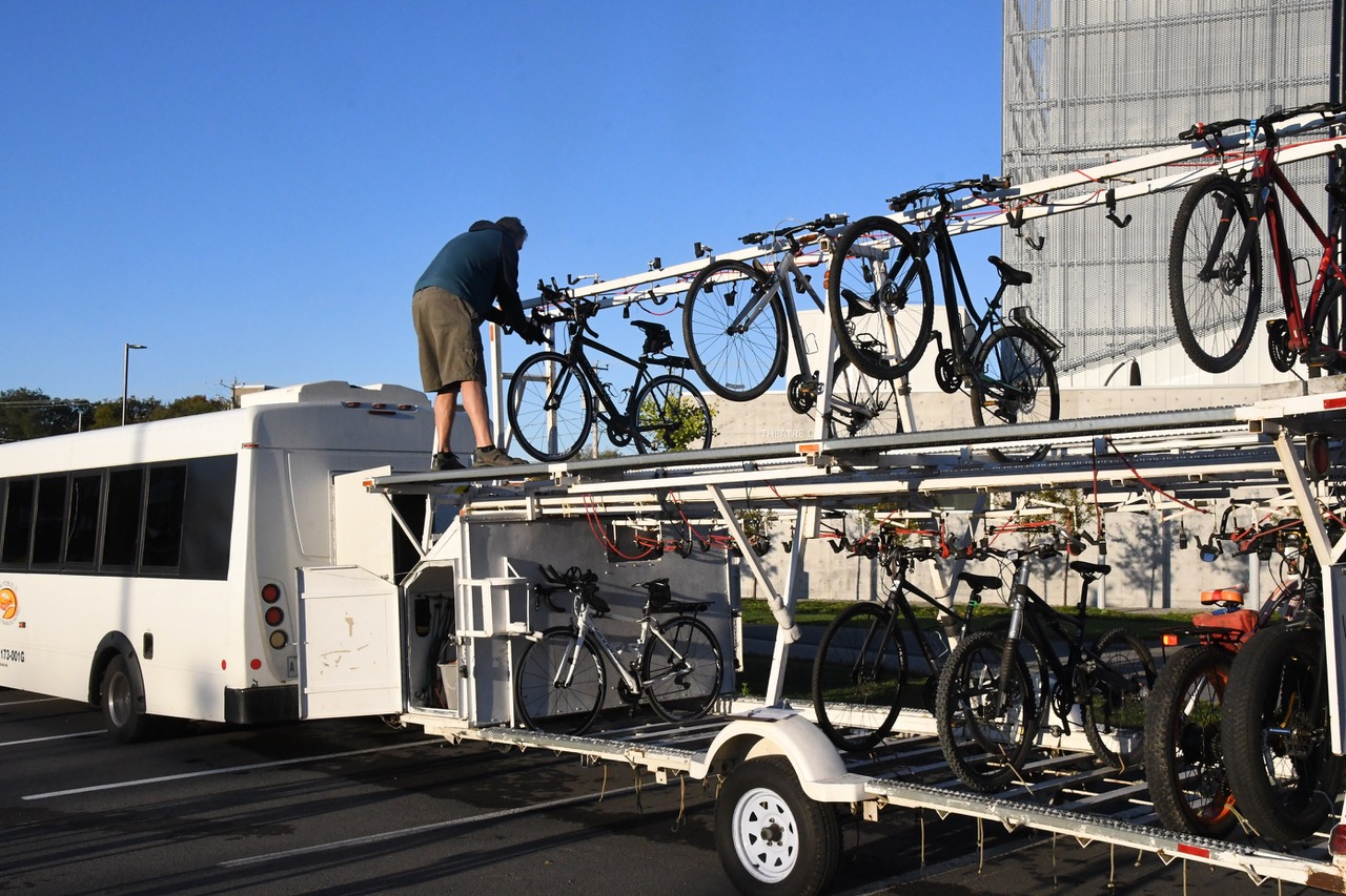 Man loading bikes and luggage aboard a P'tit du Nord bike trail shuttle