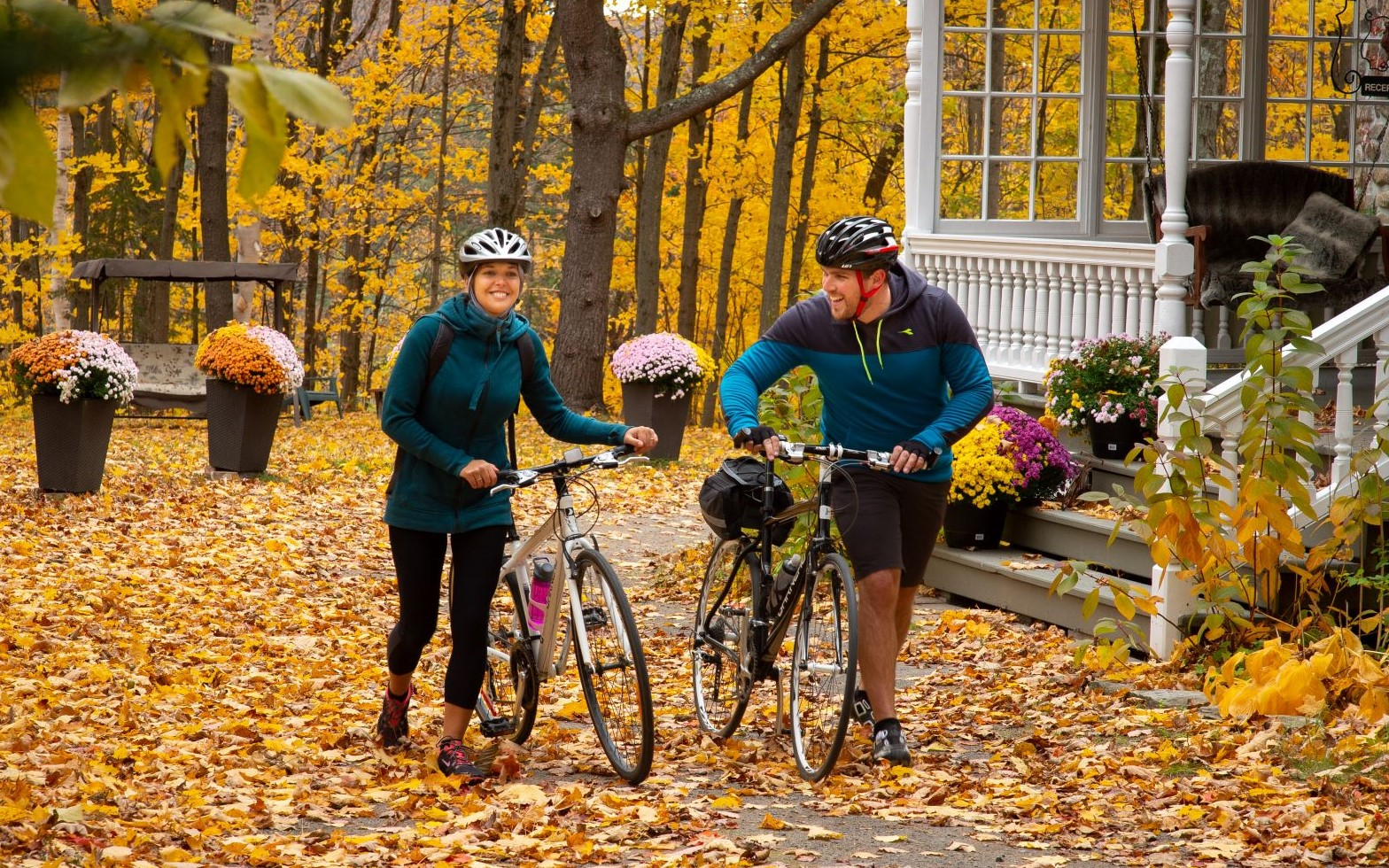 On an autumn day, two cyclists walk their bikes in front of an inn along the P'tit du Nord bike trail
