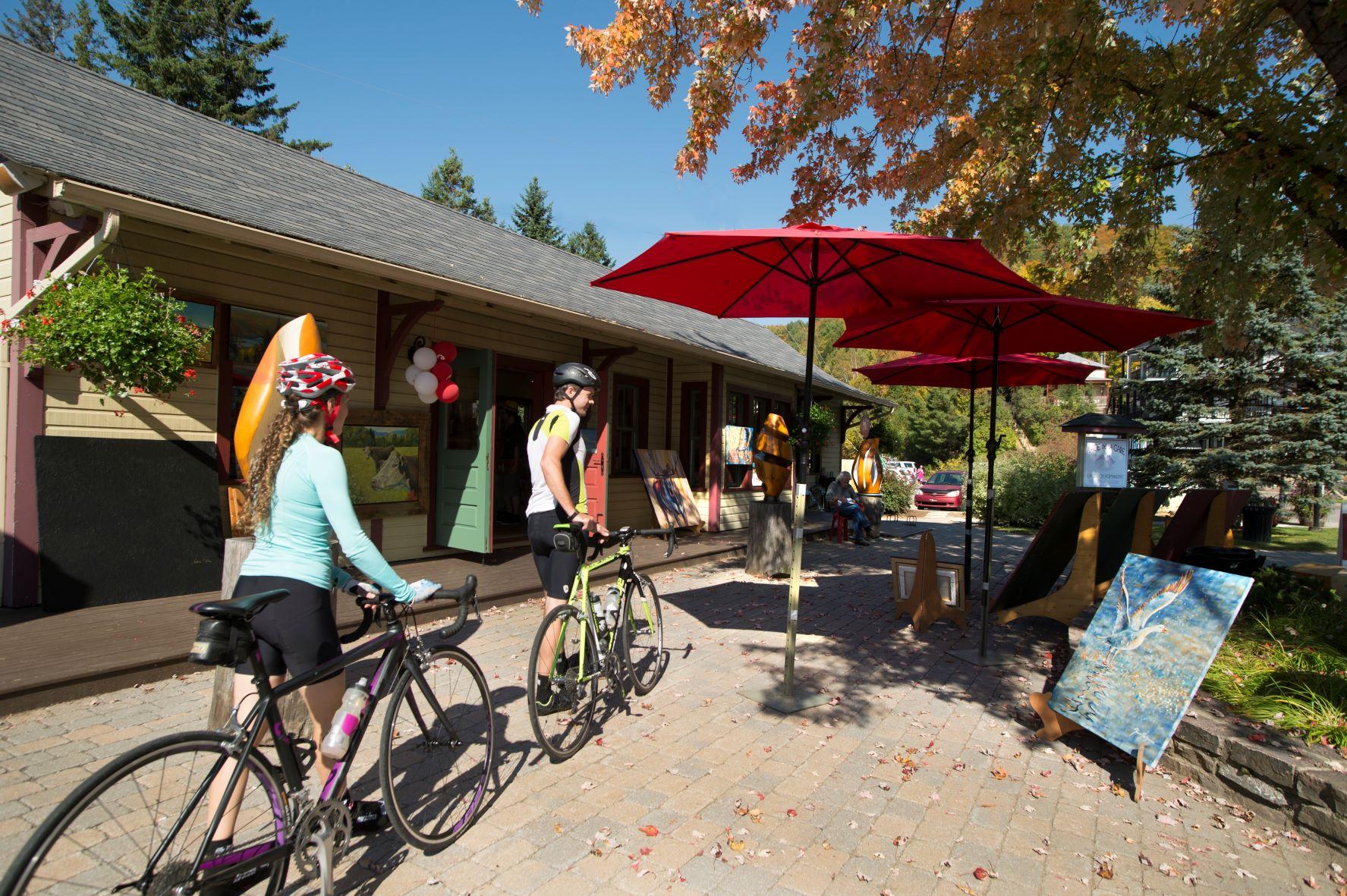 cyclists walk bikes by a train station