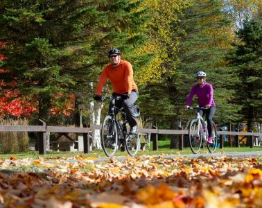 Two cyclists pedal the P'tit du Nord bike trail in autumn.